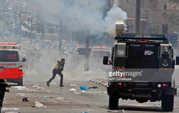 A Palestinian protester shields his face while fleeing teargas during clashes with Israeli forces after Friday prayers at the main entrance of the...