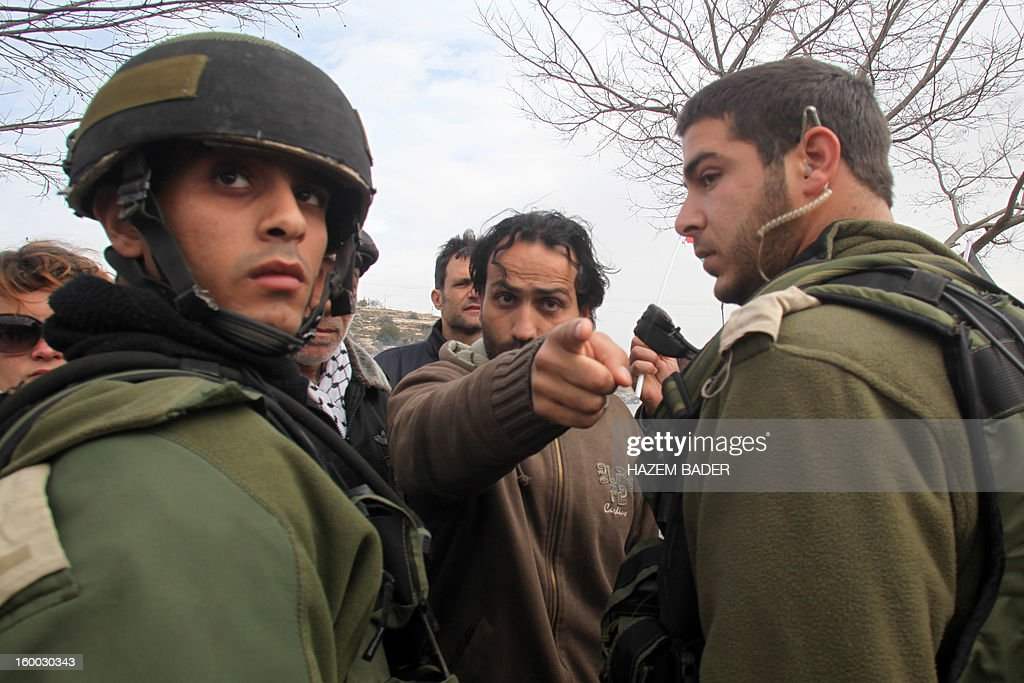 A Palestinian protester shouts gestures in front of Israeli soldiers during a protest against the Israeli occupation on the main road 60 between the West Bank cities of Bethlehem and Hebron near the Israeli settlement of Daniel on January 25, 2013. AFP PHOTO / HAZEM BADER