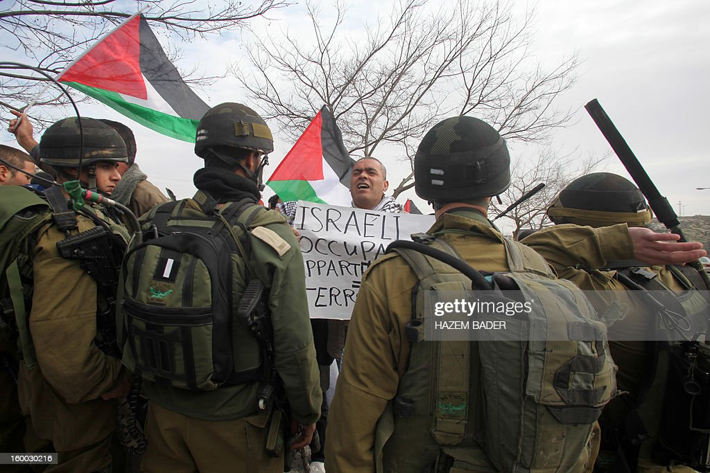 A Palestinian protester shouts holding a banner in front of an Israeli soldiers during a protest against the Israeli occupation on the main road 60 between the West Bank cities of Bethlehem and Hebron near the Israeli settlement of Daniel on January 25, 2013.