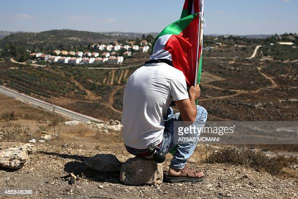 A Palestinian protester sits holding a national flag after a march against Palestinian land confiscation to expand the nearby Jewish Hallamish...