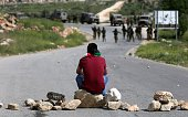A Palestinian protester sits on stones facing Israeli security forces during clashes following a demonstration against Palestinian land confiscation...