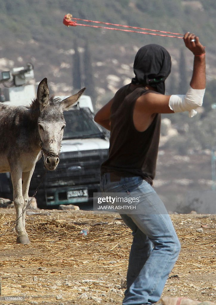 A Palestinian protester standing opposite a donkey uses a slingshot to hurl stones towards Israeli soldiers during a weekly demonstration against the expropriation of Palestinian land by Israel in the village of Kfar Qaddum near the occupied West Bank city of Nablus on September 28, 2012.