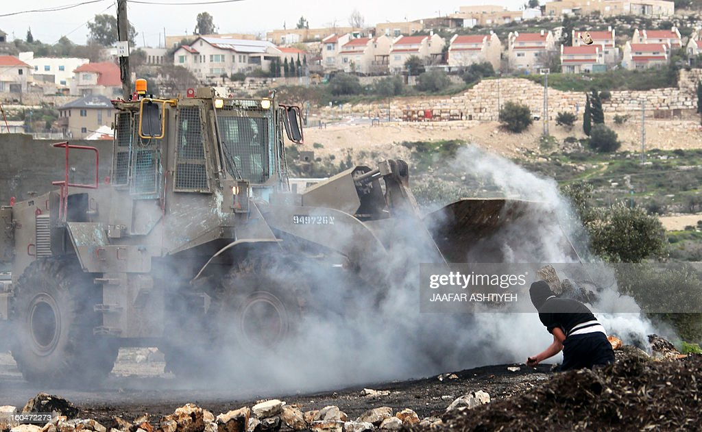 A Palestinian protester stands in front of a bulldozer during clashes following a protest against the expropriation of Palestinian land by Israel on February 1, 2013 in the village of Kafr Qaddum, near Nablus, in the occupied West Bank.