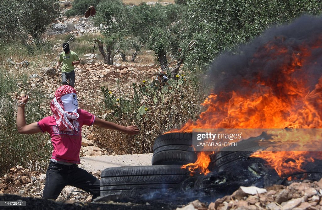 A Palestinian protester stands next to burning tyres as he throws a stone with his slingshot towards Israeli soldiers during clashes on April 18, 2012 following a demonstration against the expropriation of Palestinian land by Israel in the village of Kfar Qaddum near the occupied West Bank city of Nablus.