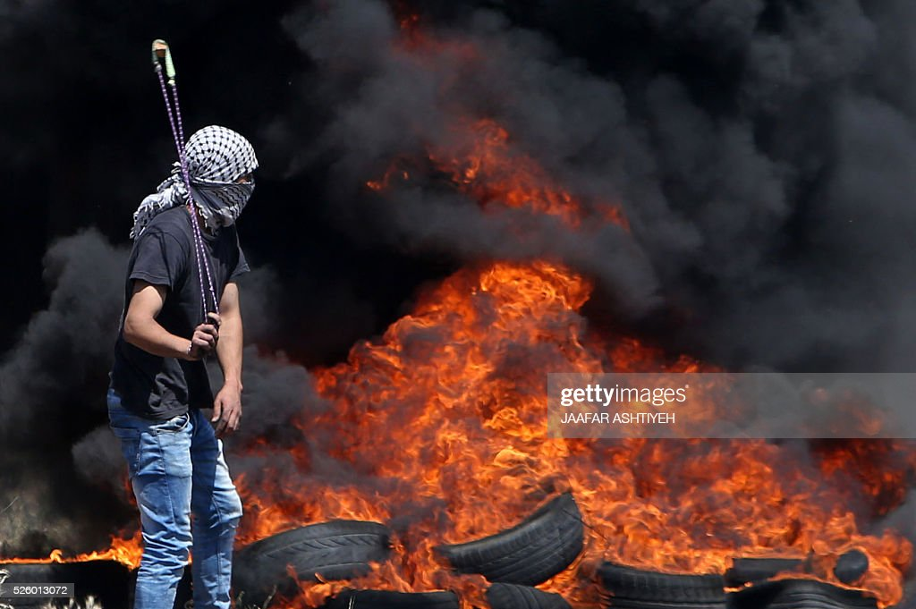 A Palestinian protester stands with a slingshot in front of burning tires during clashes with Israeli security forces following a demonstration against the expropriation of Palestinian land by Israel on April 29, 2016 in the village of Kfar Qaddum, near Nablus, in the occupied West Bank. / AFP / JAAFAR