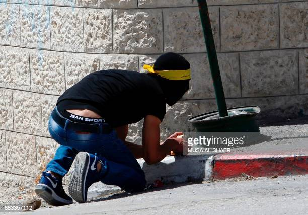 A Palestinian protester take cover during clashes with Israeli security forces following a demonstration marking the 69th anniversary of the 'Nakba'...