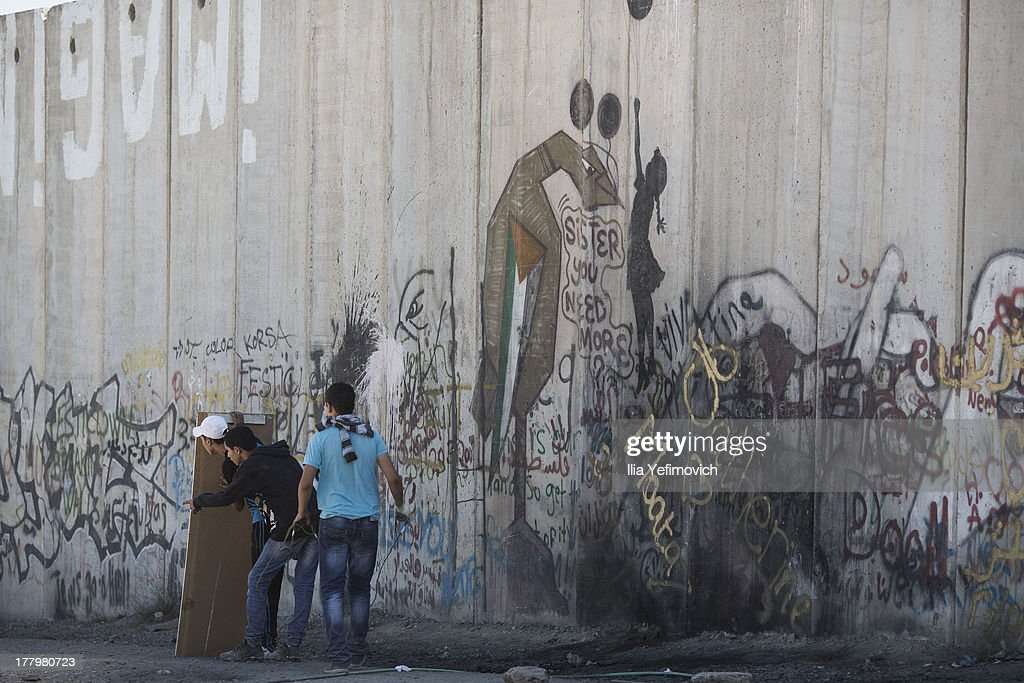 Palestinian protester take shelter during clalesh with Israel Defense Forces after the funeral held for three Palestinians killed during IDF operation at Kalandia refugee camp on August 26, 2013 in Ramallah, West Bank.