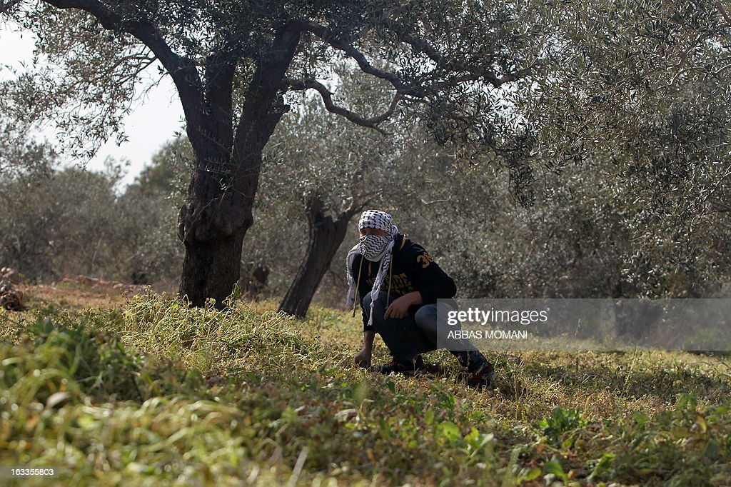 A Palestinian protester takes cover away from tear gas during clashes with Israeli soldiers following the funeral of Mohammad Asfour, a 22-year-old protester who died of wounds sustained the previous day, in the West Bank village of Abud on March 8, 2013. Asfour was wounded in the head by a rubber-coated steel bullet fired by Israeli troops during a protest which erupted after a prisoner died in Israeli custody.