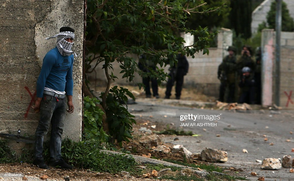 A Palestinian protester takes cover behind the corner of a building during clashes with Israeli security forces following a weekly demonstration against the expropriation of Palestinian land by Israel in the village of Kfar Qaddum, near Nablus, in the occupied West Bank, on May 6, 2016. / AFP / JAAFAR
