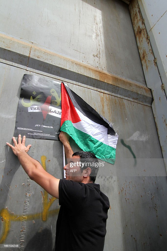 A Palestinian protester takes part in a rally marking Land Day next to Israel's controversial separation barrier at the main entrance of the West Bank town of Bethlehem on March 30, 2013. Land Day commemorates the death of six Arab Israeli protesters at the hands of Israeli troops during mass protests in 1976 against plans to confiscate land in Galilee.