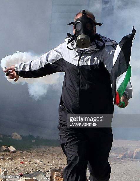A Palestinian protester throw back a tear gas canister during clashes with Israeli security forces following a demonstration against the...