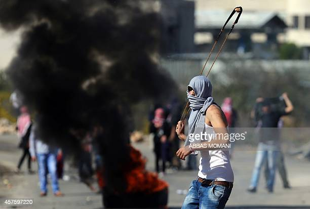 A Palestinian protester throw rocks at Israeli police vehicle during clashes at the entrance of the Israeli Ofer military prison near the West Bank...