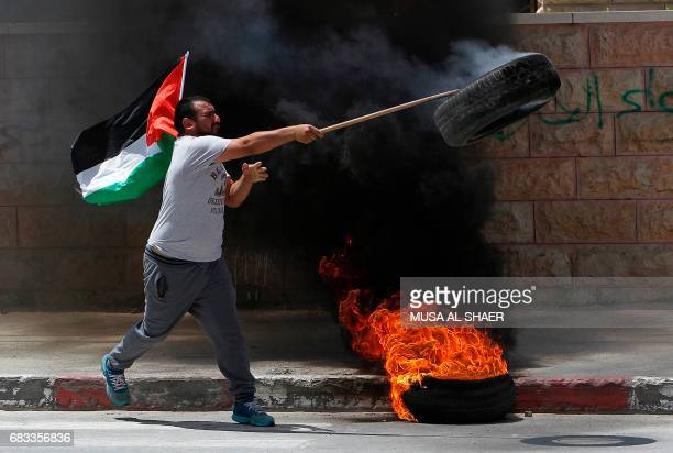 A Palestinian protester throws a burning tyre towards Israeli security forces during clashes following a demonstration marking the 69th anniversary...