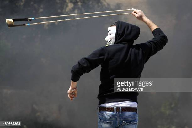 A Palestinian protester throws a rocks towards Israeli police close to the Israeli Ofer military prison in West Bank town of Betunia on April 4...