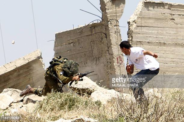 A Palestinian protester throws a stone at an Israeli soldier during a protest in AlKhader village near the town of Bethlehem in the occupied West...