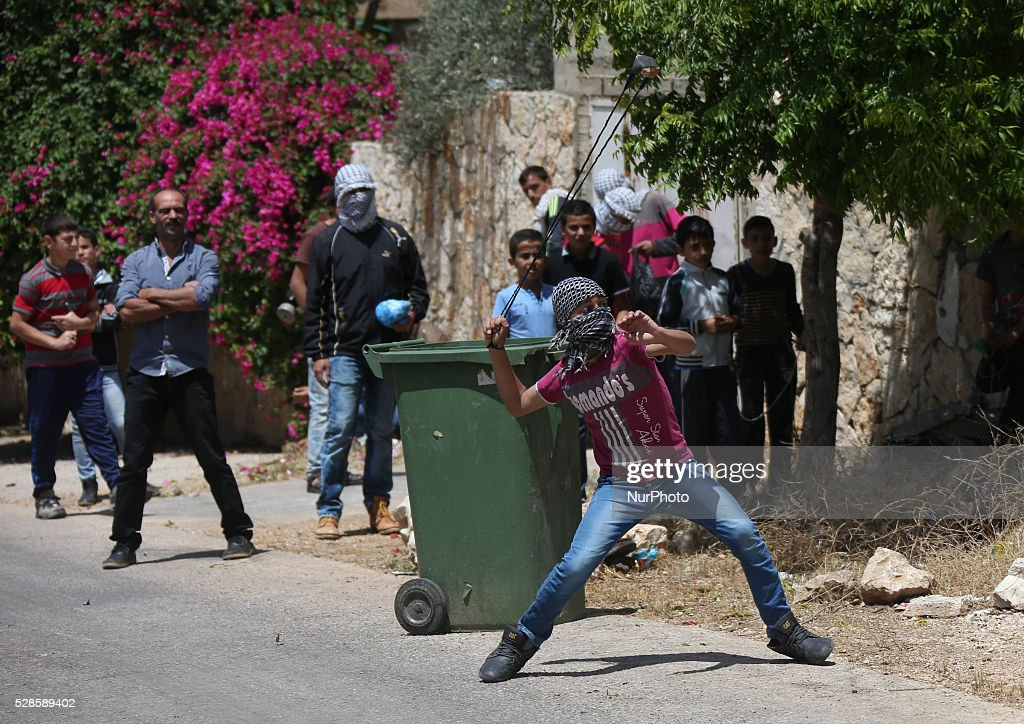 A Palestinian protester throws a stone at Israeli forces during a protest against the expanding of Jewish settlements in Kufer Qaddom village, near the West Bank city of Nablus. May 6, 2016.