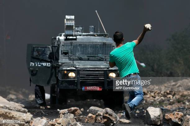 Palestinian protester throws a stone at Israeli security forces during clashes following a weekly demonstration against the expropriation of...