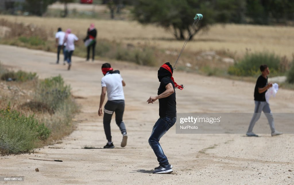 A Palestinian protester throws a stone at Israeli soldiers during clashes at a protest in support of Palestinian prisoners on hunger strike in Israeli jails, in the West Bank village of Beit Dajan, near Nablus May 19, 2017.