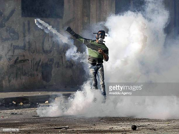 Palestinian protester throws a stone during clashes with Israeli police at Shuafat refugee camp after a Palestinian rammed his vehicle into a crowd...