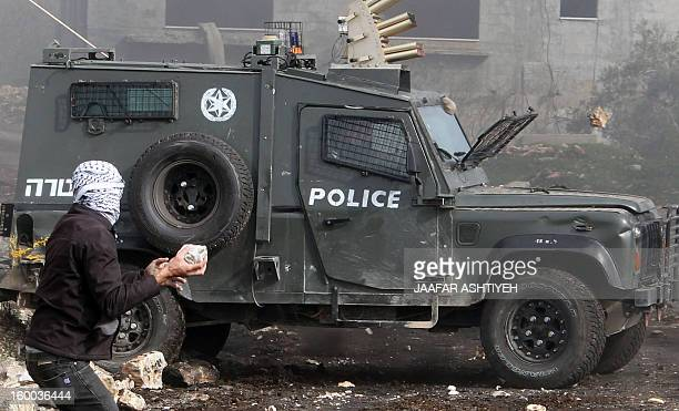 A Palestinian protester throws a stone towards an Israeli police car during a protest against the expropriation of Palestinian land by Israel on...