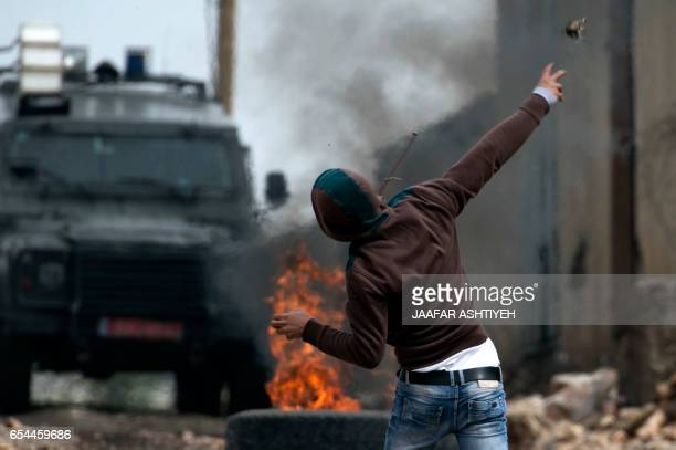 A Palestinian protester throws a stone towards Israeli security forces during clashes following a weekly demonstration against the expropriation of...