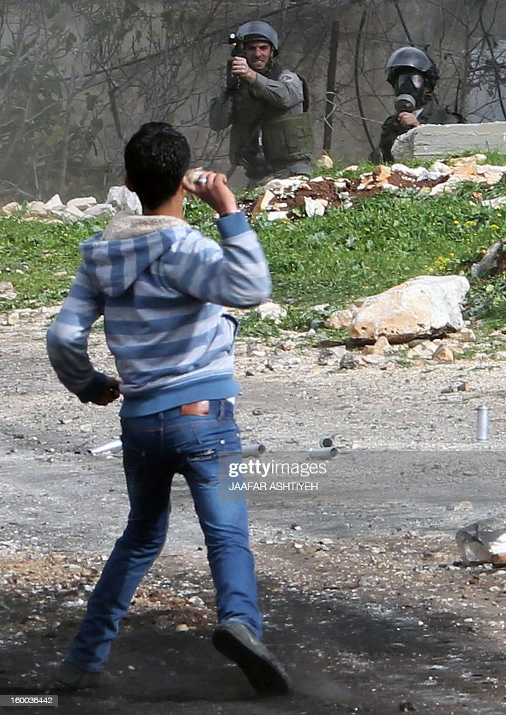 A Palestinian protester throws a stone towards Israeli soldiers during a protest against the expropriation of Palestinian land by Israel on January 25, 2013 in the village of Kafr Qadum, near Nablus, in the occupied West Bank.