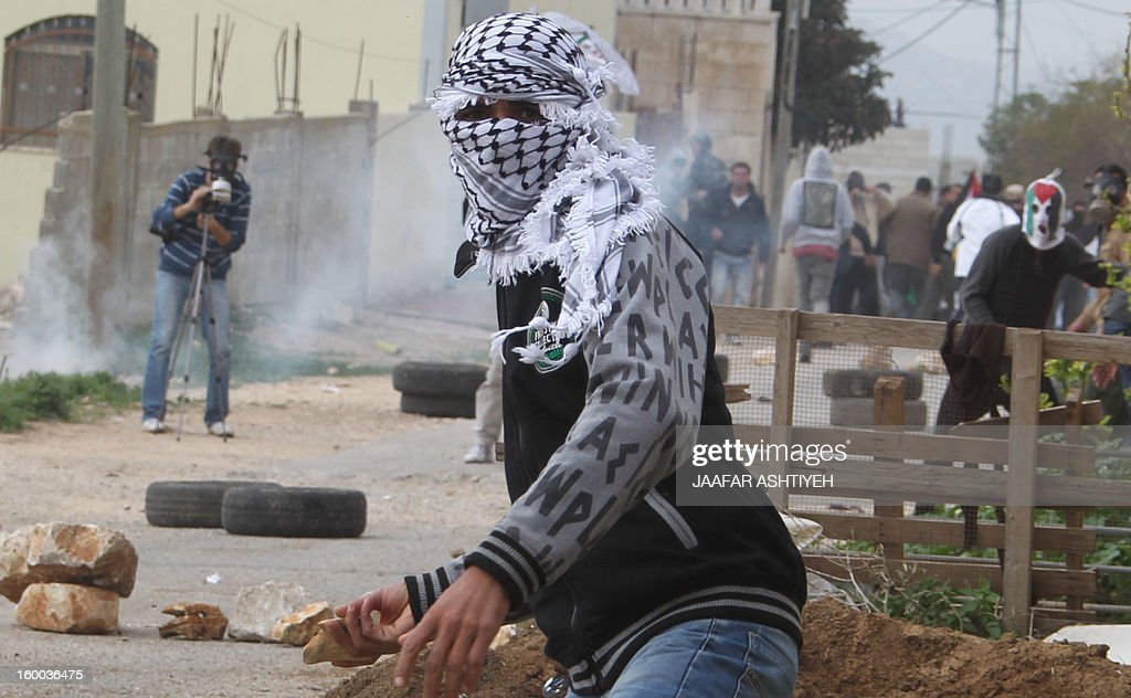 A Palestinian protester throws a stone towards Israeli soldiers during a protest against the expropriation of Palestinian land by Israel on January 25, 2013 in the village of Kafr Qadum, near Nablus, in the occupied West Bank. AFP PHOTO/JAAFAR ASHTIYEH