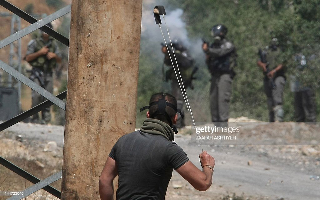 A Palestinian protester throws a stone with his slingshot as Israeli soldiers fire teargas during clashes on April 18, 2012 following a demonstration against the expropriation of Palestinian land by Israel in the village of Kfar Qaddum near the occupied West Bank city of Nablus.