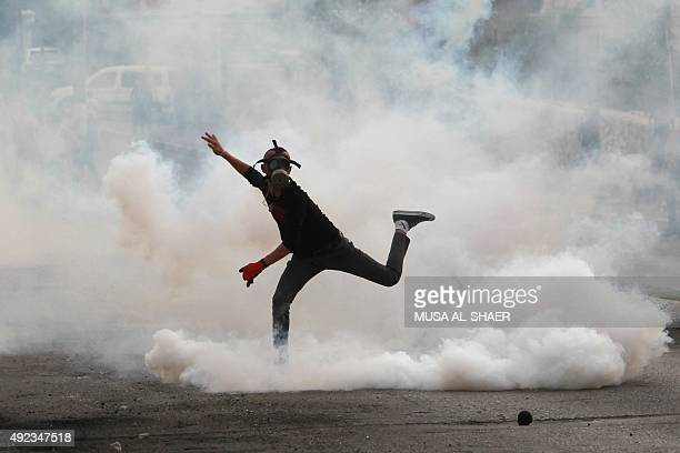 A Palestinian protester throws a tear gas canister back during clashes with Israeli security forces at the main entrance of the West Bank city of...