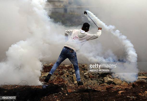 A Palestinian protester throws a tear gas canister using a sling shot during clashes with Israeli security forces at the northern entrance of the...