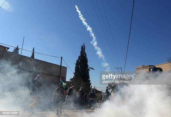 A Palestinian protester throws a teargas canister back at Israeli forces during clashes following a weekly demonstration against the expropriation of...
