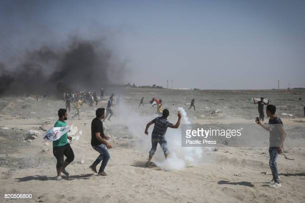 Palestinian protester throws a teargas canister fired by Israeli soldiers back during clashes on the Israeli border with Gaza Friday July 21 2017 An...