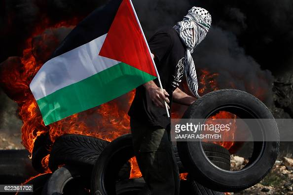A Palestinian protester throws a tire on a fire during clashes with Israeli security forces following a demonstration against the expropriation of...