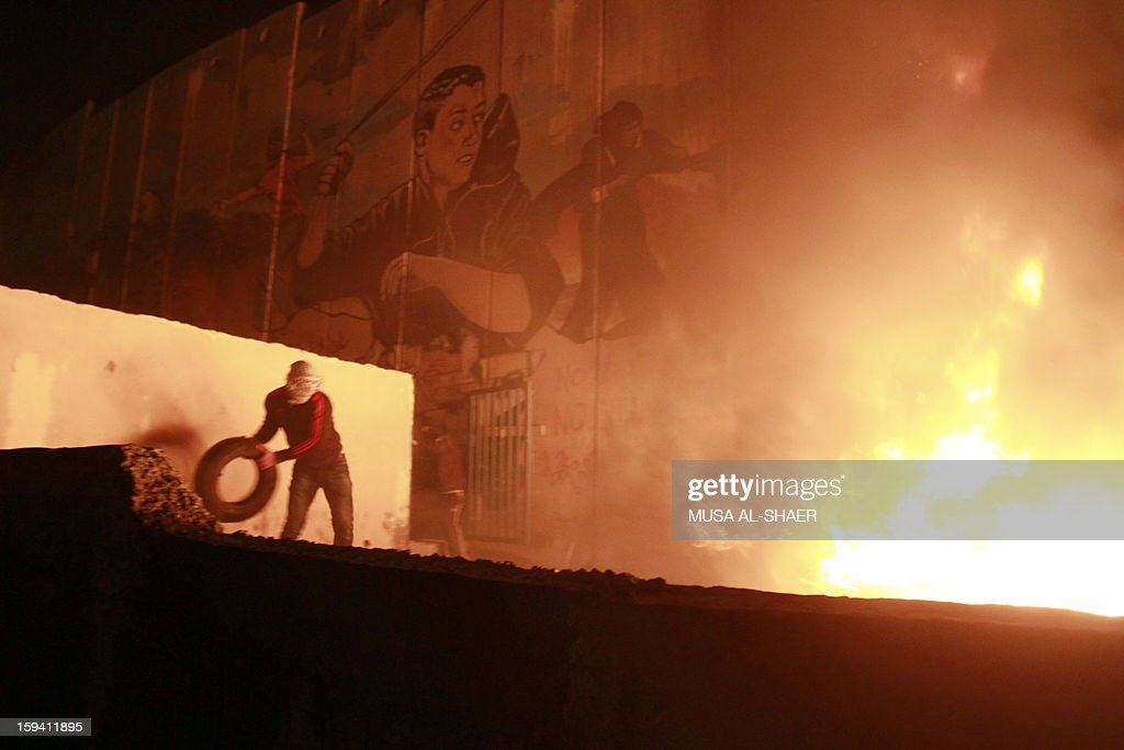 A Palestinian protester throws a tire onto a burning pile under an Israeli military observer tower at the controversial separation barrier during a protest in Aida Palestinian refugee camp near the West Bank city of Bethlehem on January 13, 2013.