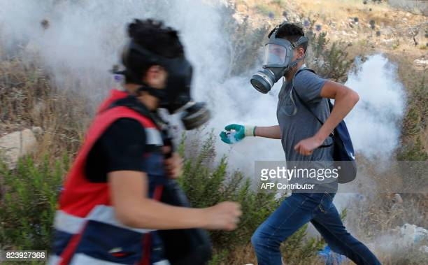 A Palestinian protester throws back a gas canister towards Israeli security forces during clashes near the Jewish settlement of Beit El on the...