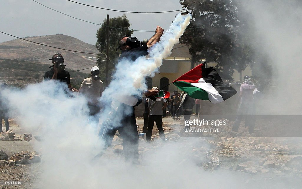 A Palestinian protester throws back a tear gas canister fired by Israeli security forces while he holds his national flag during clashes following a demonstration against the expropriation of Palestinian land by Israel in the village of Kfar Qaddum, near Nablus, in the occupied West Bank on June 6, 2013, as Palestinians across the West Bank and the Gaza Strip hold rallies to mark the Naksa (setback). Palestinians mark 'Naksa Day' to mourn the 46th anniversary of Israel's occupation of the West Bank and Gaza Strip in the Six-Day War.