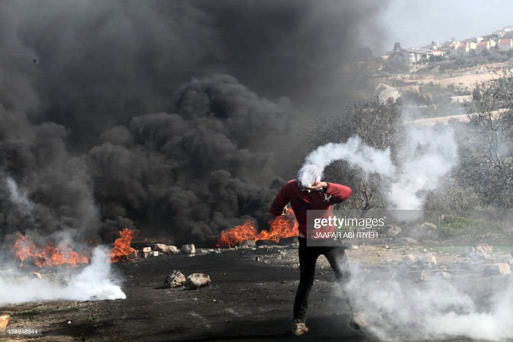 A Palestinian protester throws back a tear gas canister fired by Israeli soldiers near a cloud of black smoke rising from burning tyres during a demonstration against the expropriation of Palestinian land by Israel in the village of Kfar Qaddum, near the occupied West Bank city of Nablus, on January 4, 2013. AFP PHOTO/JAAFAR ASHTIYEH