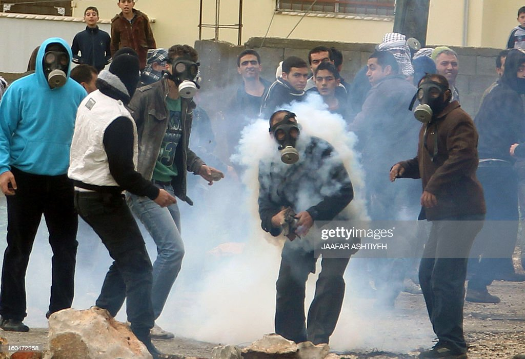 A Palestinian protester throws back a tear gas canister to Israeli soldiers during clashes following a protest against the expropriation of Palestinian land by Israel on February 1, 2013 in the village of Kafr Qaddum, near Nablus, in the occupied West Bank.