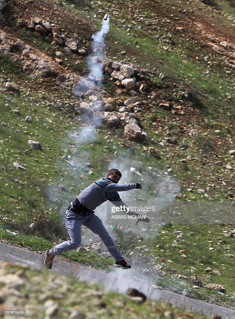 A Palestinian protester throws back a tear gas canister towards Israeli soldiers during clashes following a demonstration against the expropriation of Palestinian land by Israel in the West Bank village of Nabi Saleh on December 7, 2012. AFP PHOTO / ABBAS MOMANI