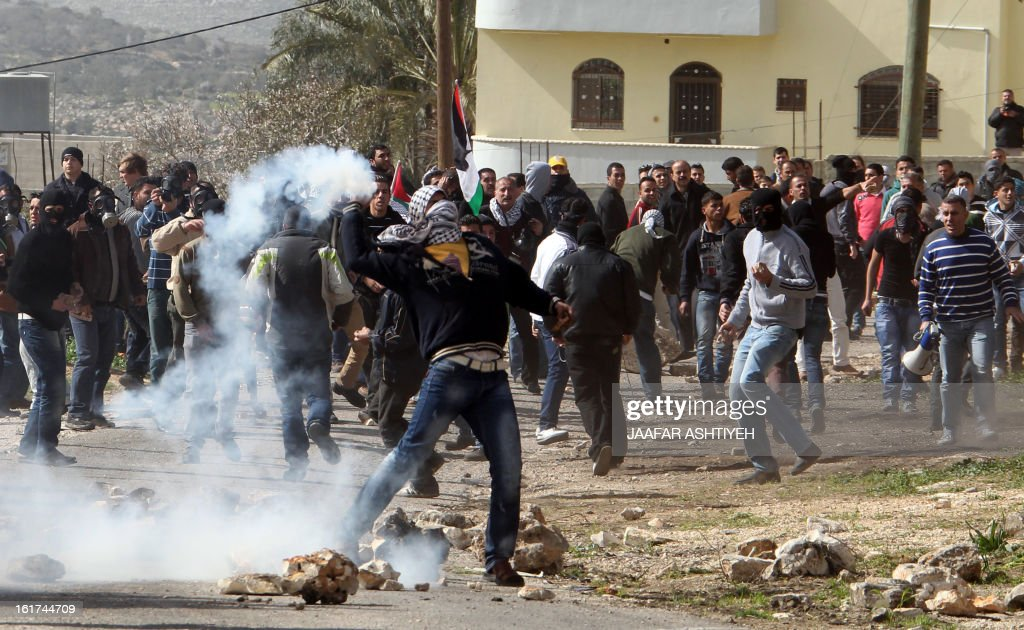 A Palestinian protester throws back a tear gas canister towards Israeli soldiers during clashes following a protest against the expropriation of Palestinian land by Israel on February 15, 2013, in the village of Kafr Qaddum, near the occupied West Bank city of Nablus. AFP PHOTO/JAAFAR ASHTIYEH