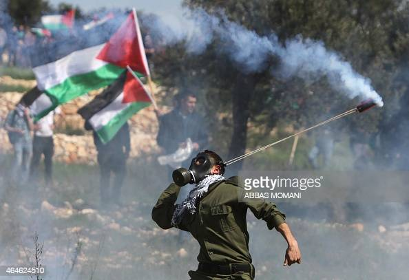 A Palestinian protester throws back a tear gas cannister using a sling shot during clashes with Israeli security forces on February 27 2015 following...