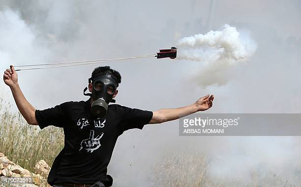 A Palestinian protester throws back a tear gas cannister using a sling shot during clashes with Israeli security forces on April 17 2015 following a...