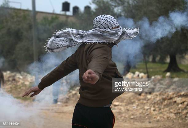 A Palestinian protester throws back a teargas cannister towards Israeli security forces during clashes following a weekly demonstration against the...