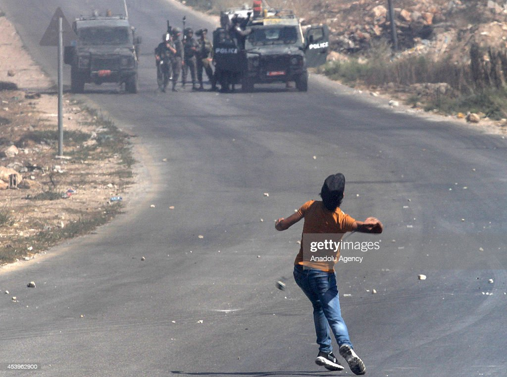 A Palestinian protester throws stone to Israeli security forces during an anti-Israel protest in Nablus, West Bank on 22 August, 2014.