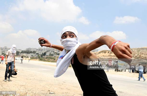 Palestinian protester throws stone to the Israeli security forces during a demonstration held to support the Palestinian prisoners in Israeli jails...