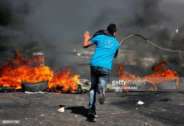 A Palestinian protester throws stones during clashes with Israeli security forces following a protest marking the 69th anniversary of the Nakba which...