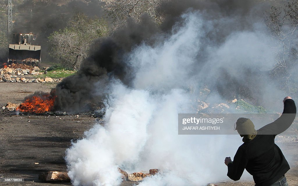 A Palestinian protester throws stones towards an Israeli maned bulldozer during clashes following a demonstration against the expropriation of Palestinian land by Israel in the village of Kfar Qaddum, near the occupied West Bank city of Nablus, on December 28, 2012. AFP PHOTO / JAAFAR ASHTIYEH