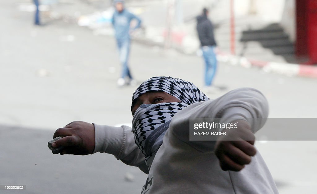 A Palestinian protester throws stones towards Israeli security forces during clashes following a protest against the expropriation of Palestinian land by Israel on March 1, 2013, near the israeli settlement of Hagay in the West bank town of Hebron. AFP PHOTO/ HAZEM BADER