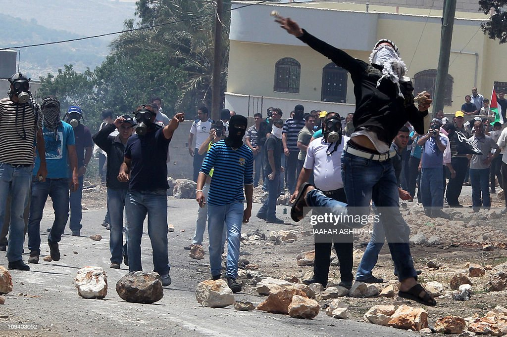 A Palestinian protester throws stones towards Israeli security forces during clashes following a protest against the expropriation of Palestinian land by Israel on May 24, 2013 in the village of Kafr Qaddum, near the occupied West Bank city of Nablus.