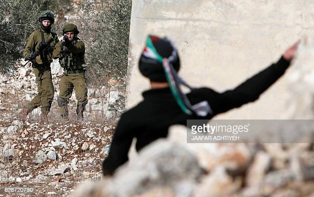 Palestinian protester throws stones towards Israeli security forces during clashes following a demonstration against the expropriation of Palestinian...
